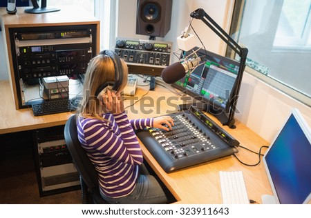 Female radio host operating sound mixer at desk in studio - stock photo