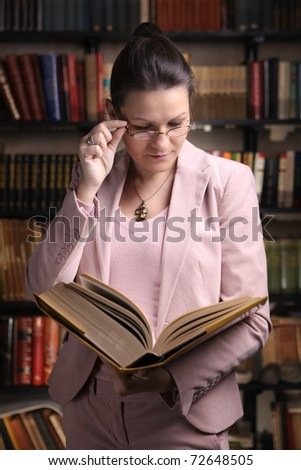 Female reading a thick old book in front of colorful bookshelf - stock photo