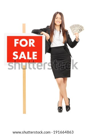 Female real estate agent holding money by a for sale sign isolated on white background - stock photo