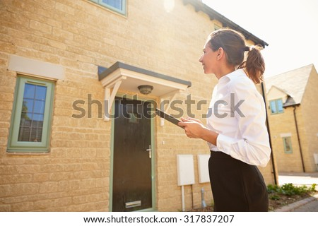 Female real estate agent looking at a house exterior - stock photo