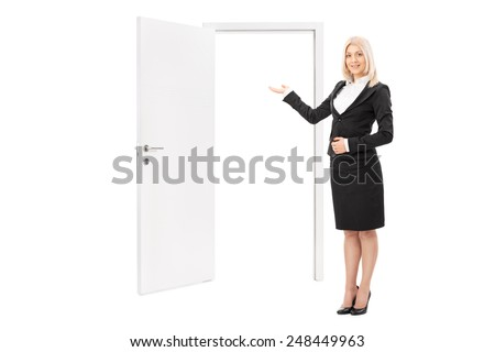 Female real estate agent pointing towards a door isolated on white background - stock photo