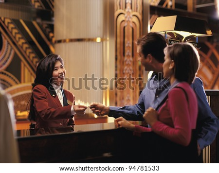 Female receptionist giving room key to couple - stock photo