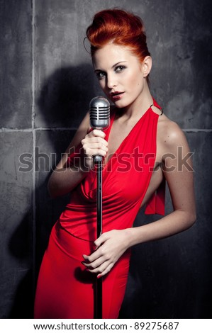 Female redhair singer red dress - stock photo