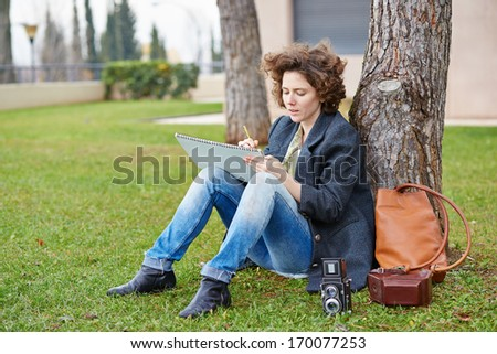 Female redhead art student drawing outdoors at college campus - stock photo