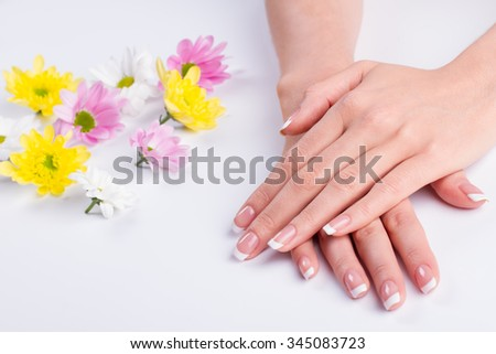 Female relaxation and care. Beautiful nails with a French manicure. Beauty salon. Spa treatments for hands.  - stock photo