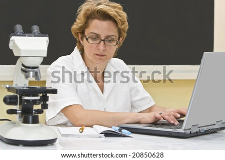 Female researcher analyzing data on a laptop in a laboratory. - stock photo