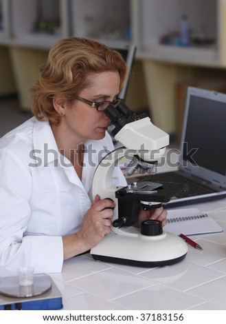 Female researcher looking through microscope in a laboratory. - stock photo