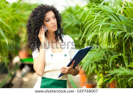 Female researcher talking on the phone in a greenhouse  - stock photo