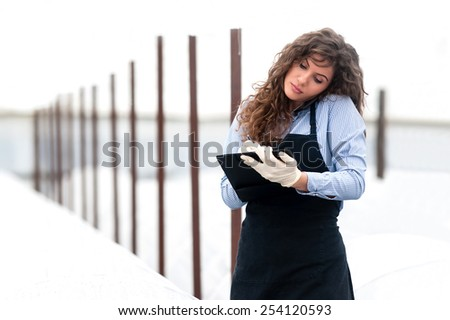 Female researcher technician studying with a clipboard, pen and gloves, dressed in office clothes,office shirt and apron, talking on the phone in all withe greenhouse. - stock photo