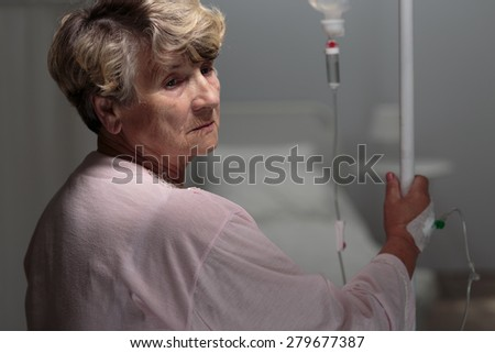 Female retiree walking with an IV drip - stock photo