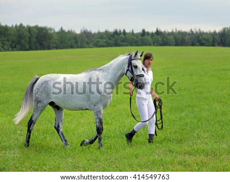 Female rider walking with horse - stock photo