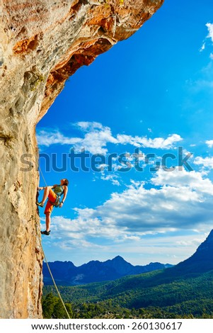 female rock climber climbs on a rocky wall - stock photo
