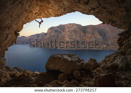 Female rock climber on a cliff in a cave at Kalymnos, Greece - stock photo