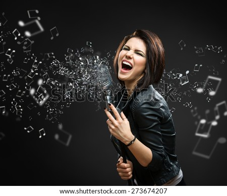 Female rock musician holding sounding mike with melody in the air on grey background - stock photo