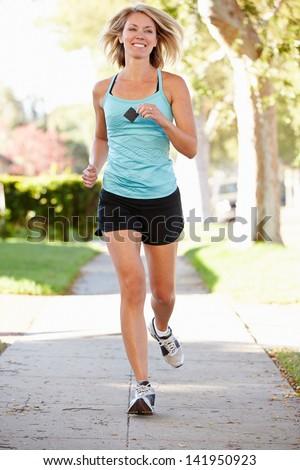 Female Runner Exercising On Suburban Street - stock photo