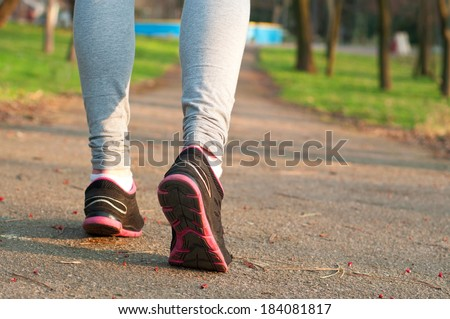 Female runner feet running on the road outdoors at nature. Closeup, main focus on the shoe. On a bright sunny spring day - stock photo