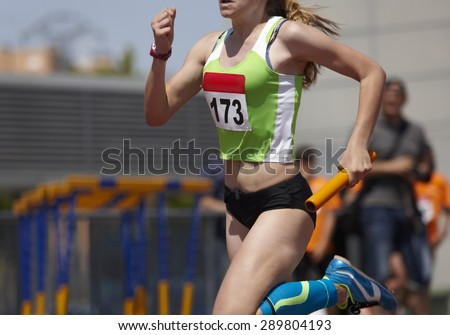 Female runner finalizing a relay race in a running track. Horizontal - stock photo
