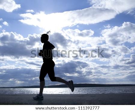 Female runner full length silhouette against the blue sky and sun - stock photo