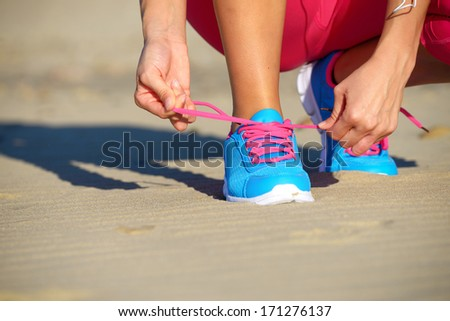 Female runner getting ready for running challenge workout on beach. Female athlete tying the laces of her sport shoes. - stock photo