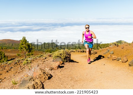 Female runner jogging and exercising outdoors in nature, rocky trail footpath on La Palma, Canary Islands - stock photo