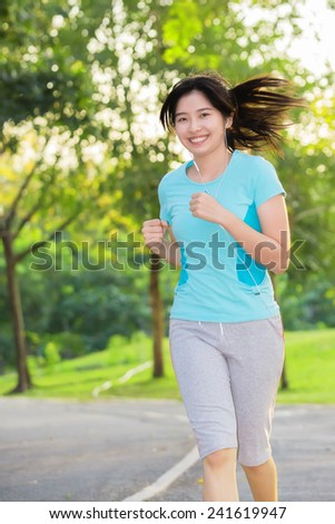 Female Runner Jogging during Outdoor Workout in a Park - stock photo