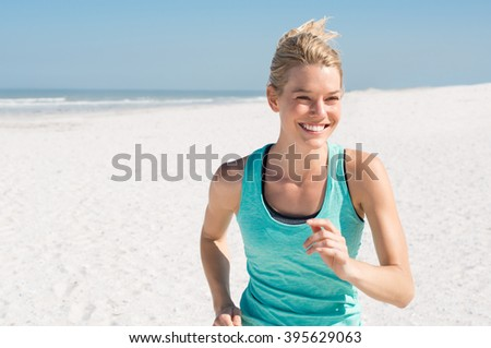 Female runner jogging during the morning on beach. Beautiful young woman running at summer morning. Beautiful fitness girl exercising outdoors. - stock photo