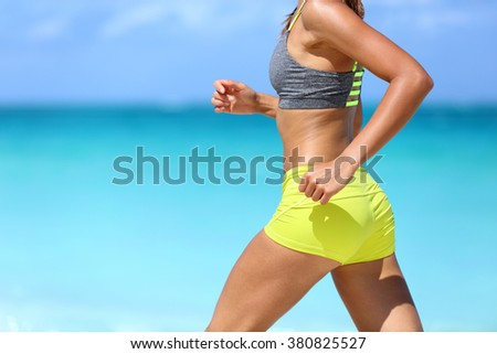 Female runner on beach with sports bra and shorts. Midsection closeup of body of a woman athlete running with speed fast training cardio wearing neon yellow activewear outfit. Active lifestyle. - stock photo