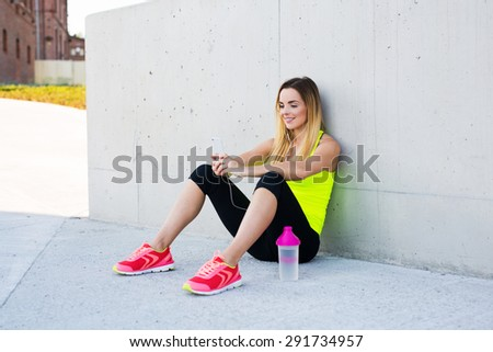 Female runner resting after workout, holding smartphone in her hands and listening to music - stock photo