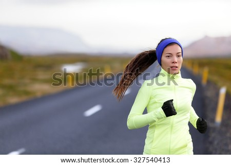 Female runner running in warm clothing for winter and autumn outside. Woman runner training in cold weather living healthy active lifestyle. - stock photo