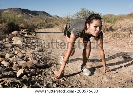 Female Runner Set to Race on a Desert Trail - stock photo