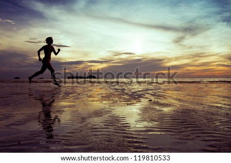 Female runner silhouette on the beach - stock photo