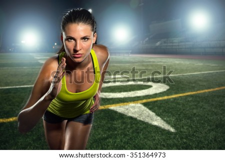 Female runner sprinter exercising and training intense track and football field athlete determination for greatness in sports - stock photo