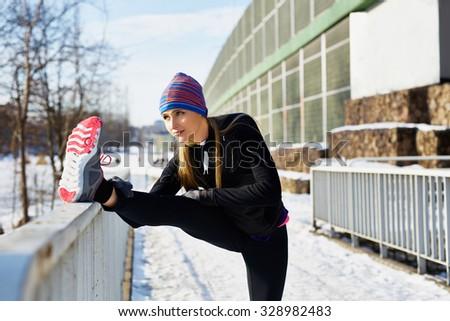Female runner stretching before running at winter - stock photo