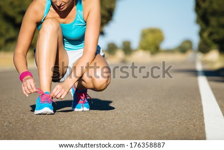 Female runner tying sports shoes laces for running on road. Athlete getting ready for training. - stock photo