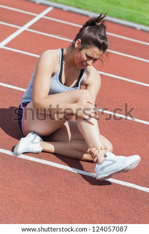 Female runner with ankle injury on track - stock photo