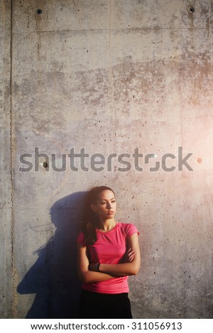 Female runner with hands crossed standing against concrete wall background with copy space area for your text message or advertising content,athletic woman taking break after fitness training outdoors - stock photo