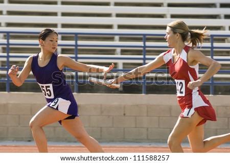 Female runners passing baton in relay race - stock photo