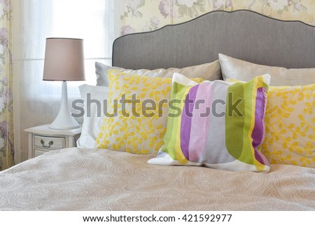 female's bedroom with colorful pillows on bed in vintage style bedroom. - stock photo