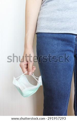 female's hand holding medical mask - stock photo