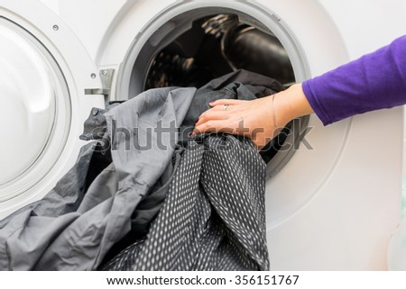 female 's hands putting  dirty clothes into washing machine - stock photo