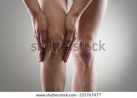 Female's healthy legs. Woman touching her injured knee. Rheumatism or  arthritis concept. - stock photo