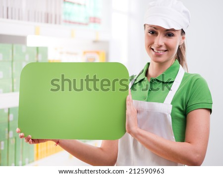 Female sales clerk holding a green sign and smiling with supermarket shelf on background. - stock photo