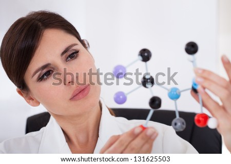 Female Scientist Concentrating On Dna Molecular Structure In Laboratory - stock photo