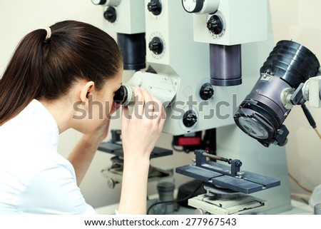 Female scientist looking through a microscope in laboratory - stock photo