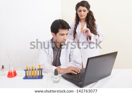 female scientist performing scientific test while her colleague taking notes on laptop. - stock photo