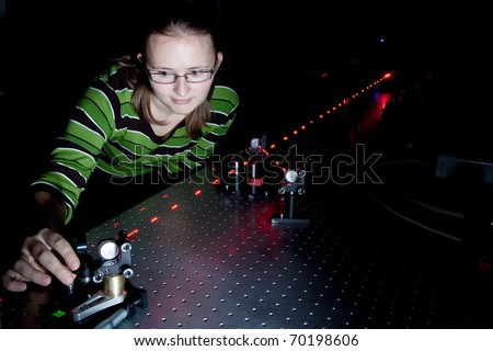 female scientist using lasers while doing research in a quantum optics lab - stock photo