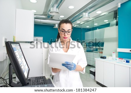 female scientist writing notes in a laboratory  - stock photo