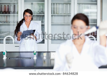 Female scientist writing on a clipboard while her colleague is pouring a liquid in a tube - stock photo