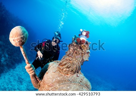 Female SCUBA Diver and a Large Underwater Statue - stock photo