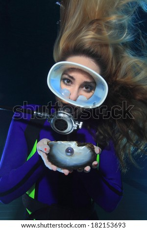 Female scuba diver and shell with pearl - stock photo